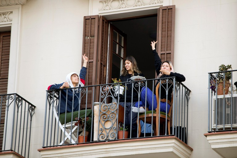 Barcelona, Spain. 22nd Mar 2020. People enjoy a lunch from their balcony. Spanish Prime Minister, Pedro Sanchez announced that the lockdown will extend for 15 days more. Spain faces the eight day of national lockdown in an effort to slow down the spread o