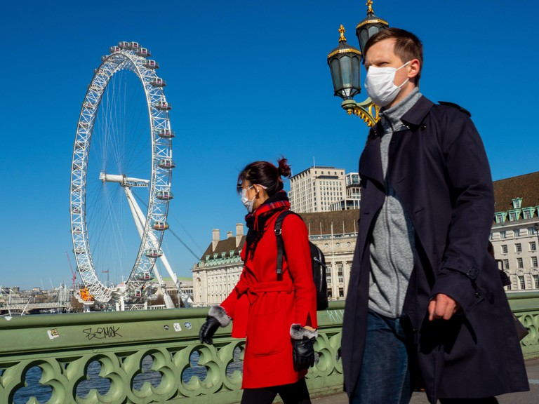 People in face masks walk near the London Eye on Sunday 22nd MArch shortly before London waslocked down due to Coronavirus.