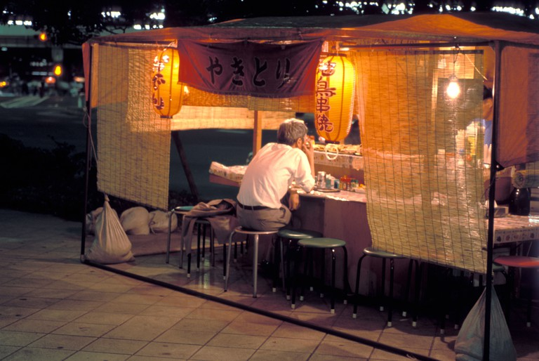 A man stops by at a sidewalk street yatai food stall