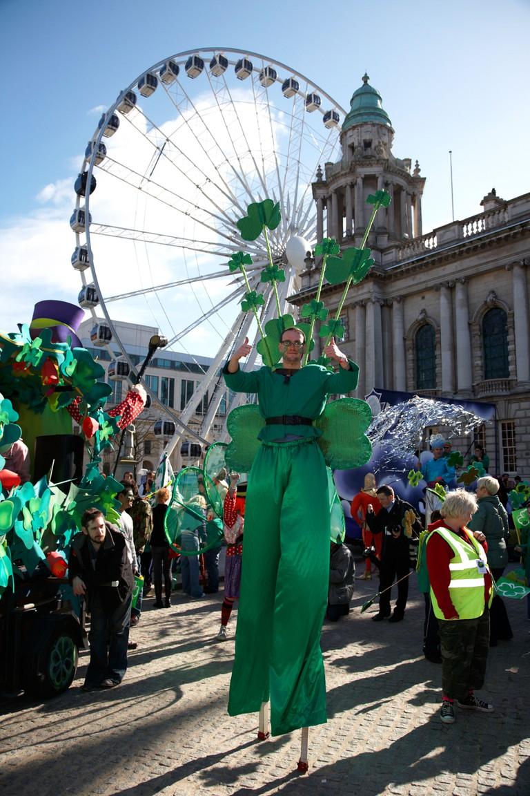Stilt walker dressed in green wearing shamrocks at St Patricks day carnival