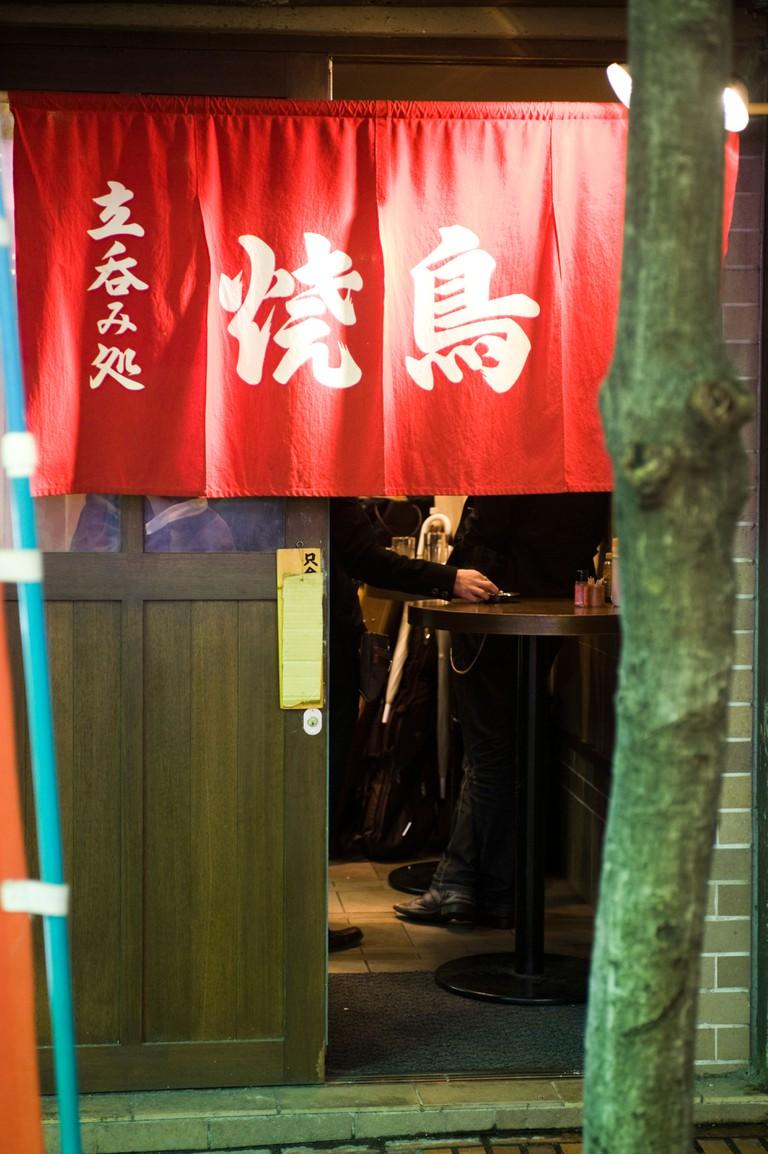 Men standing in a bar in Shinjuku, Tokyo, Japan.