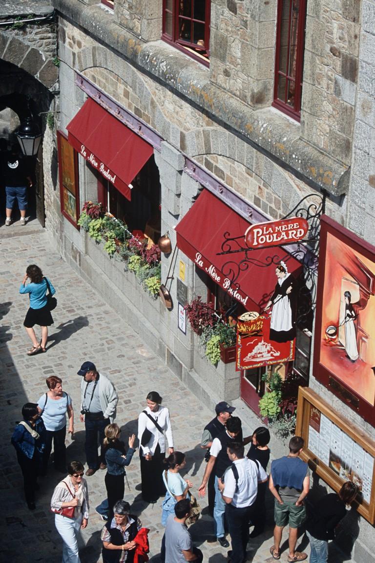 Birdseye view of tourists walking outside La Mere Poulard Restaurant, Le Mont Saint Michel, Normandy, France