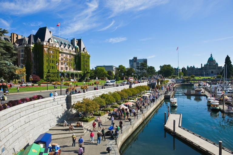 tourists walk along harbor waterfront on summer afternoon, Victoria, British Columbia, Canada