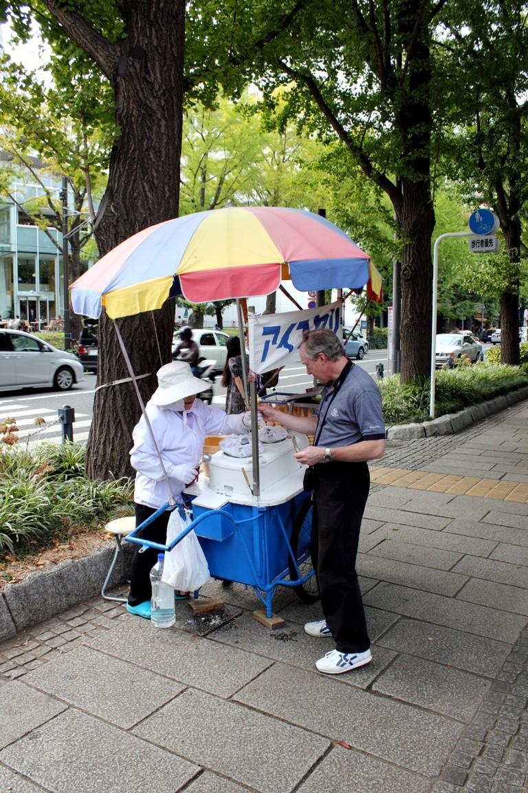 Man buys ice cream at a street cart in Yokohama, Japan.