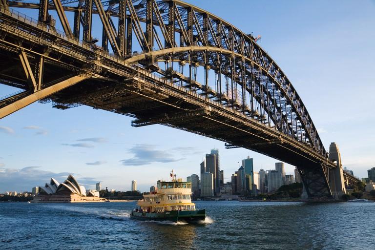 A ferry passes under Sydney Harbour Bridge