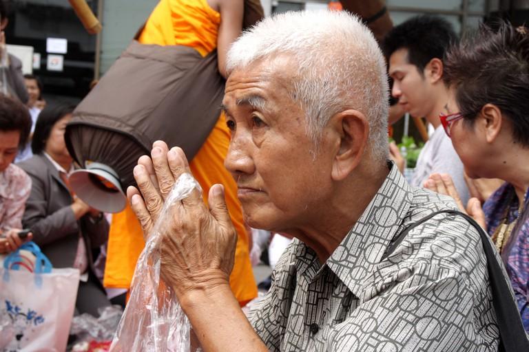 Old Thai man in Thai traditional greeting, Wai