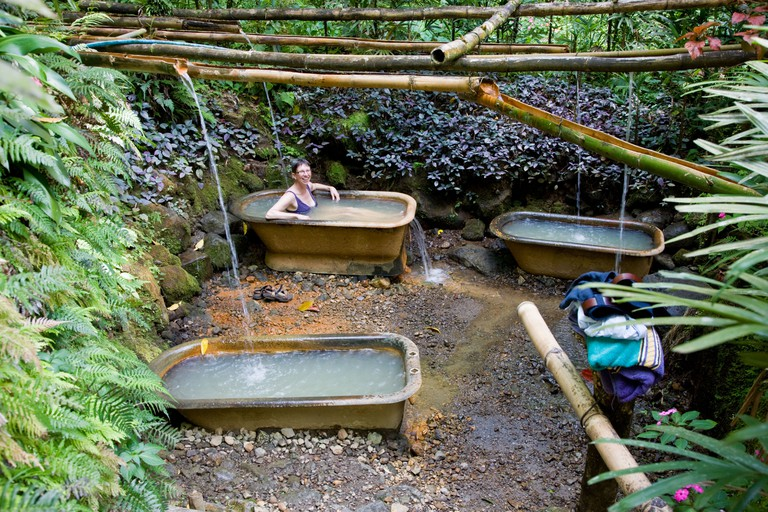 A woman relaxes in a hot volcanic sulphur spring bathtub at Ti Kwen Glo Cho near Wotten Waven in Dominica West Indies