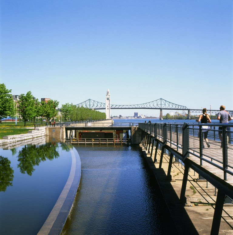Runners people jogging along the Lachine Canal and St. Lawrence River with a view of the Jacques Cartier bridge Montreal Quebec Canada  KATHY DEWITT. Image shot 05/2012. Exact date unknown.