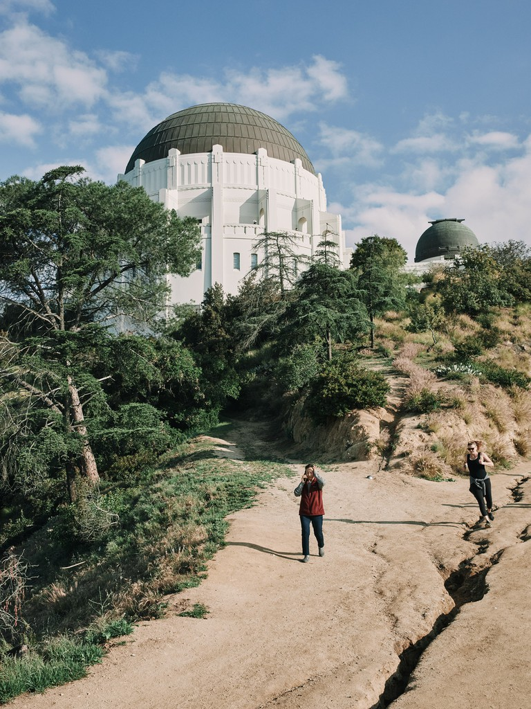 Two people hike on a trail under the Griffith Observatory