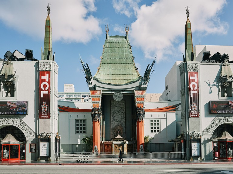 A man walks in front of the TCL Chinese Theatre, Hollywood Walk of Fame on Hollywood Boulevard in Los Angeles