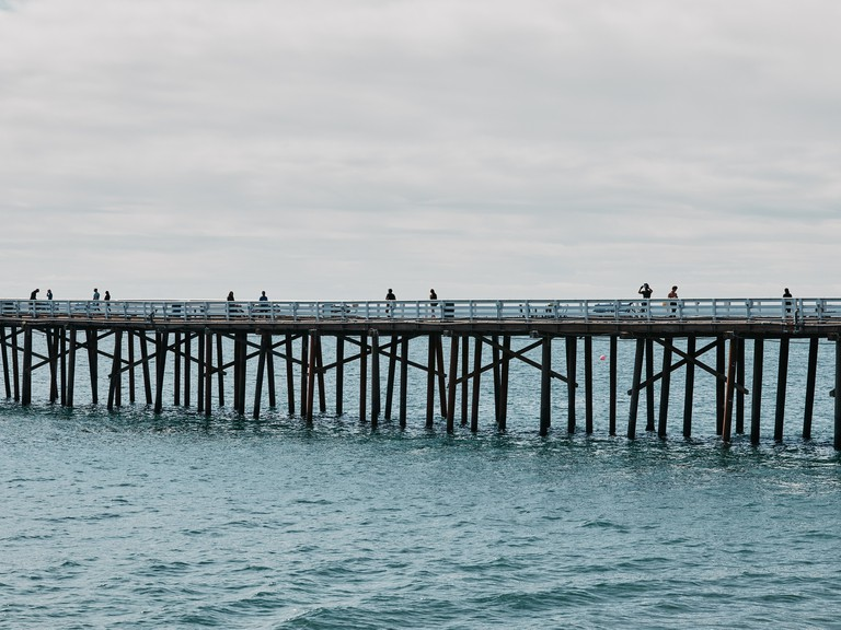 People stand on the Malibu Pier