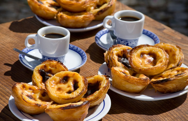 Pasteis de Nata or Pasteis de Belem; custard tarts, on a cafe table outdoors with bica coffees; Belem, Lisbon, Portugal. Image shot 2016. Exact date unknown.