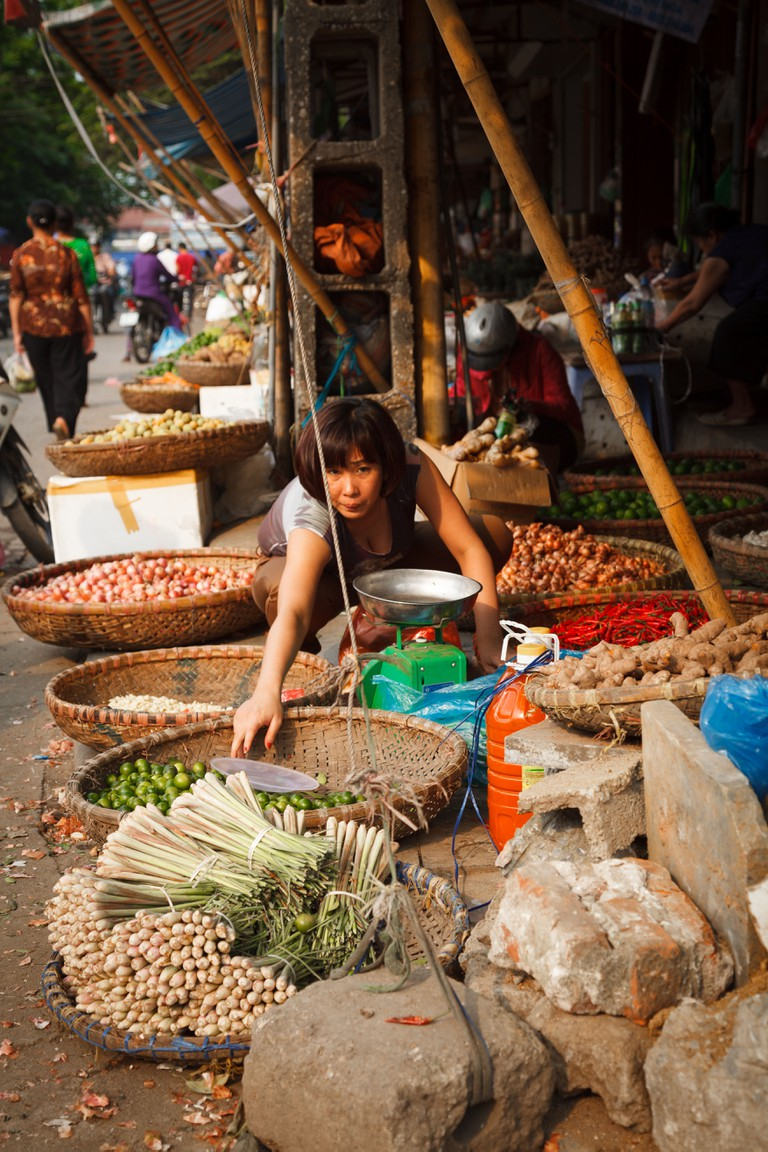 A market vendor selling vegetables and spices outside the Dong Xuan Market in the Old Quarter, Hanoi