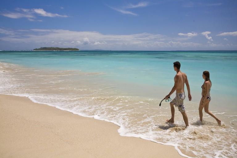 Tourists walking along beach, Cayos Zapatillas (Zapatillas Keys), Bocas del Toro Province, Panama