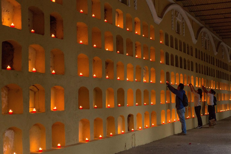 Oaxaca, Oaxaca, Mexico. 1st Nov, 2014. Young volunteers places candles on the niches in the crypt at the San Miguel cemetery during the Day of the Dead Festival known in spanish as D'a de Muertos on November 1, 2014 in Oaxaca, Mexico. © Richard Ellis/ZUMA