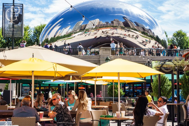Chicago Illinois Loop Millennium Park Park Grill restaurant alfresco dining outdoor umbrellas yellow Cloud Gate The Bean artist Anish Kapoor public ar