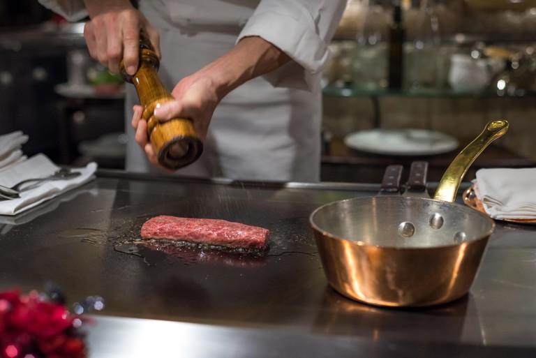 Chef cooking wagyu beef in Japanese teppanyaki restaurant