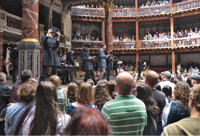 People watching performers on the stage at Globe Theatre
