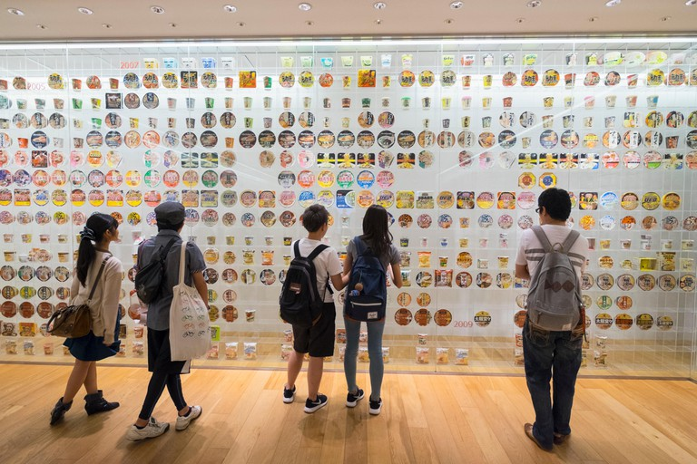 Interior display of historic cup noodle brands and packaging at Cup Noodle Museum of Yokohama, Japan.