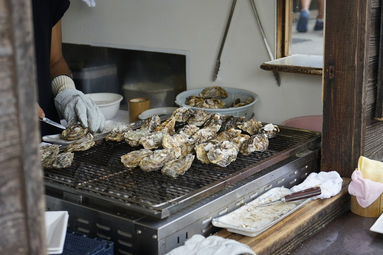 Person preparing oysters at restaurant in Itsukushima