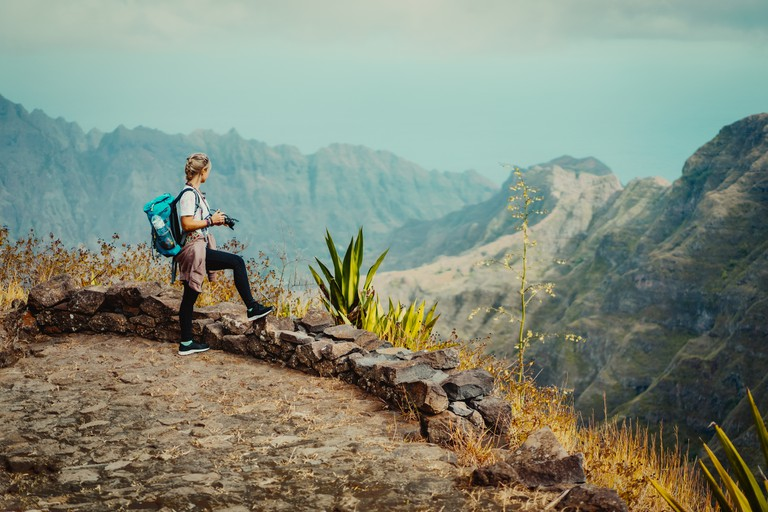 Santo Antao Island Cape Verde. Female tourist with backpack enjoying hiking path route view to Caculi valley Ribeira