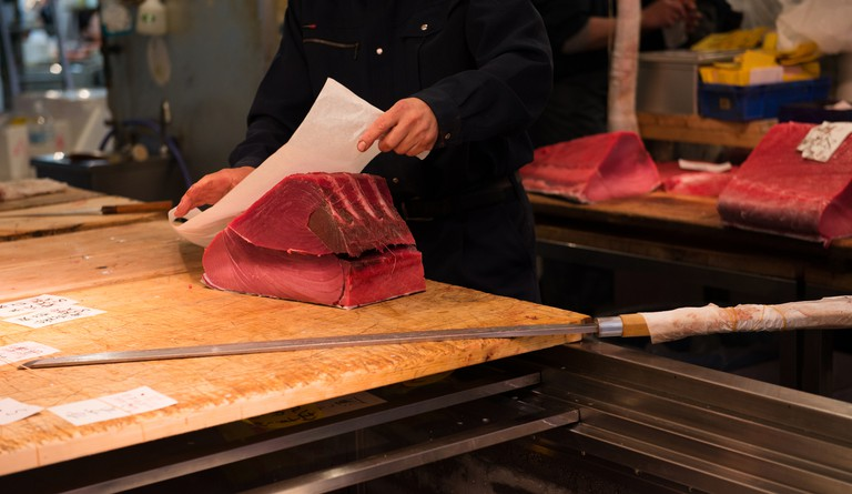 Fishmonger cutting a piece of red tuna in a market