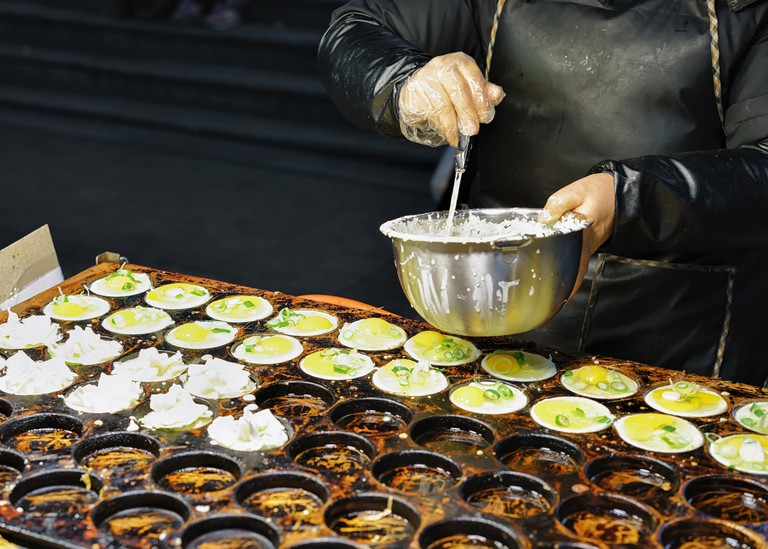 Person is cooking food in Myeongdong open street market in Seoul, South Korea