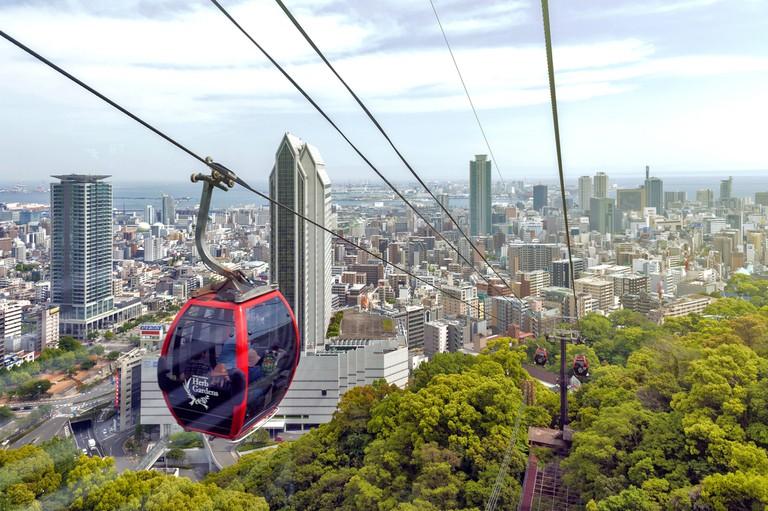 Kobe cityscape and skyscraper seen from ropeway to Nunobiki Herb Garden on Mount Rokko in Kobe, Japan