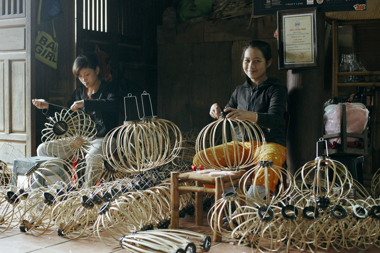 Vietnamese woman making lanterns in a shop in Hoi An, Vietnam.