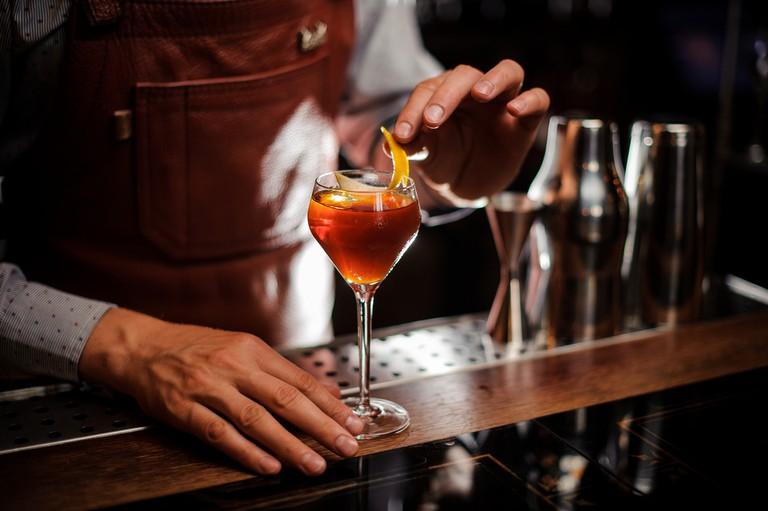 Bartender with glass and lemon peel preparing cocktail at bar