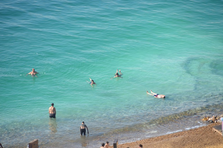 People swim and float in the Dead Sea