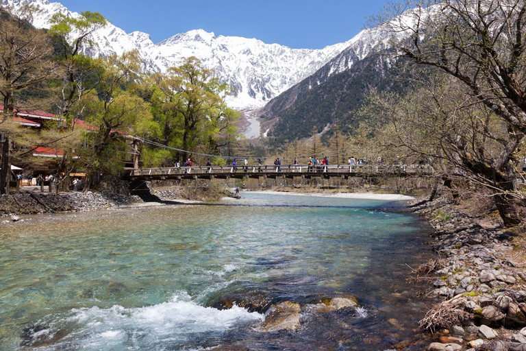 People using the Kappa Bridge to cross the Azusa river in the popular hiking area of Kamikochi