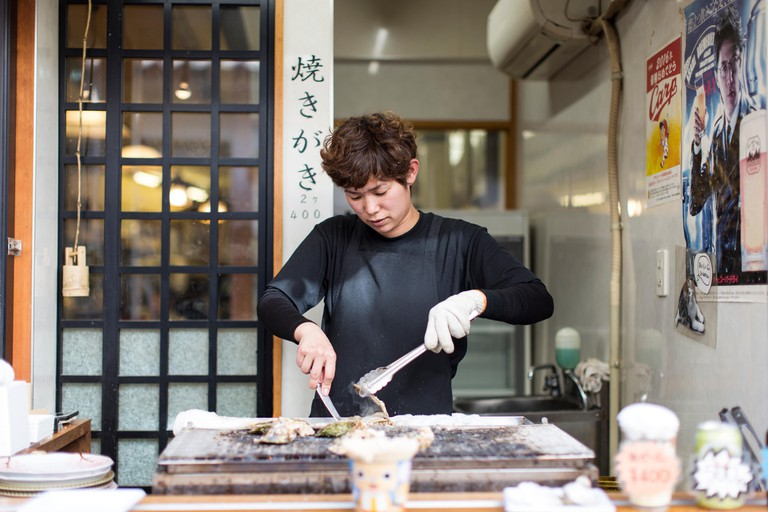 A woman preparing food in a restaurant in Japan