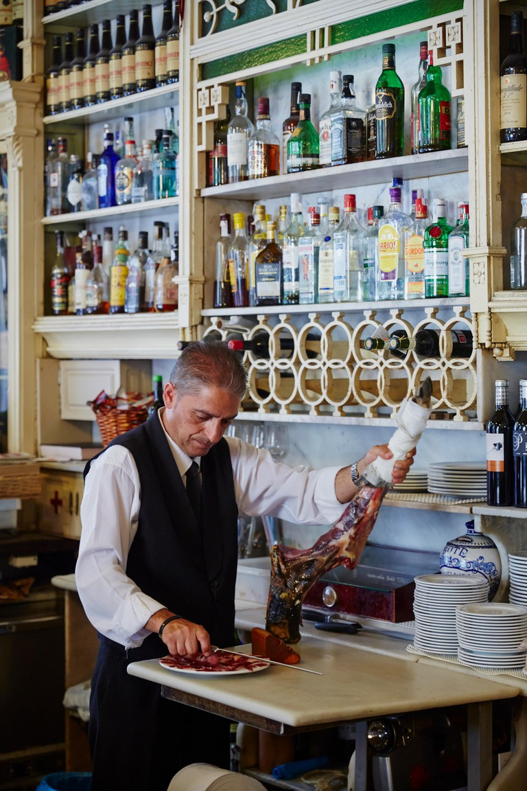 A waiter slices Iberian ham at El Rinconcillo, said to be the oldest bar in Seville.