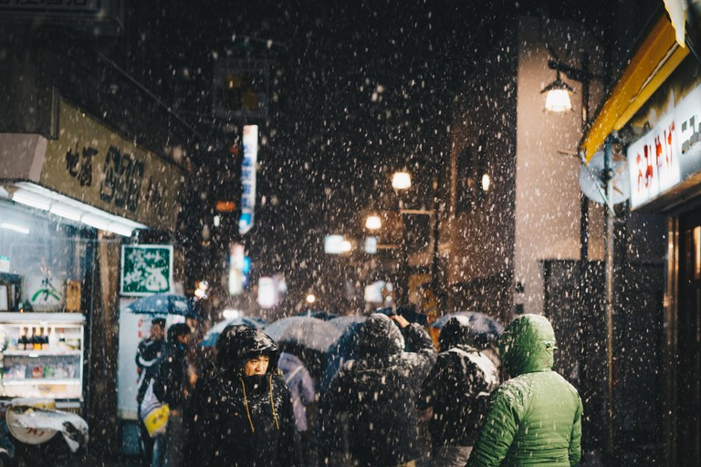 Snowing at night time in the Main Street of Nozawa Onsen as a crowd of people walk around.