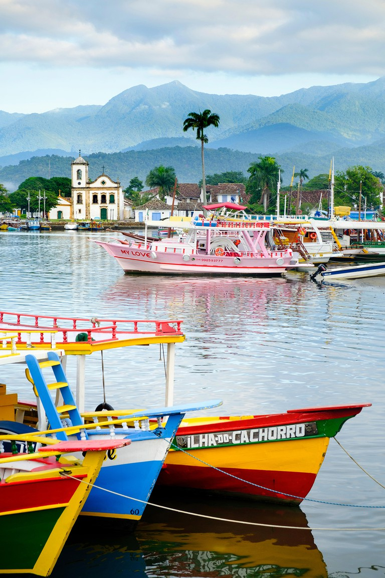 Fishing boats in Paraty village with the mountains of the Serra da Bocaina behind, Rio de Janeiro state, Brazil