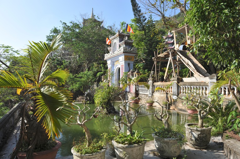 View of pool with gate of pagoda. Linh Ung Non Nuoc Pagoda. Da Nang.