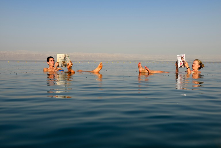 Young couple read a newspaper while floating in the Dead Sea