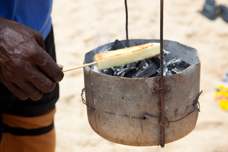 Queijo Coalho Grelhado: kebabed coalho cheese grilled over buckets filled with hot charcoal, a beach snack in Trancoso in the state of Bahia, Brazil.