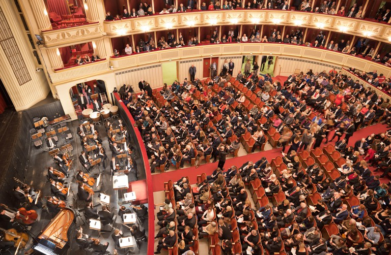 Interior of the Vienna State Opera auditorium with audience getting ready for the performance.