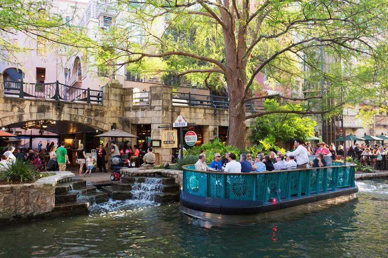 Tourists enjoying a boat trip, San Antonio River Walk, San Antonio, Texas USA