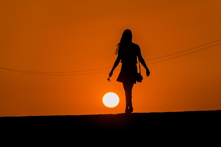 A young female tourist walks on the stone walls, surrounding the colonial walled city, during the sunset in Cartagena, Colombia.