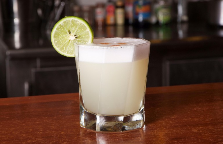 Peruvian cocktail called Pisco Sour made of Pisco Peruvian grape schnaps , lime juice, syrup, egg white, and some angostura bitter drops on top