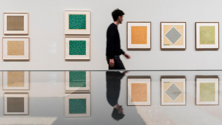 A visitor walks by screen prints and studies by Anni Albers.