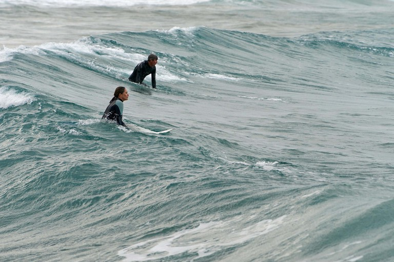 Two surfers emerging on the backside of a wave, after duck-diving under it - one man and one woman - surfing at Turners Beach, Yamba, NSW, Australia.