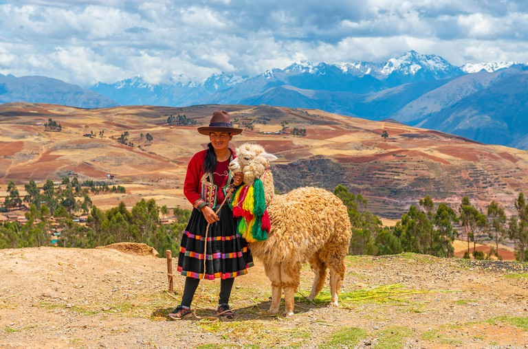 Indigenous Peruvian Quechua lady in traditional clothing with her alpaca in the Sacred Valley of the Inca and the Andes mountain range, Cusco, Peru.