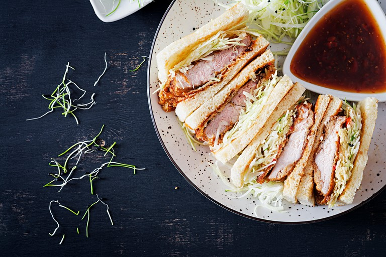 Japanese sandwich with breaded pork chop, cabbage and tonkatsu sauce.