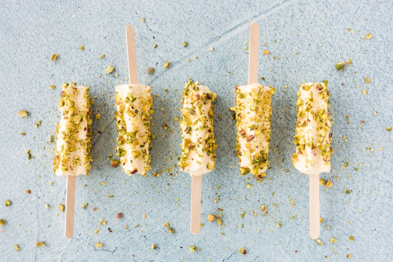 Mango and pistachio kulfi lollies on blue cement background. Top view.