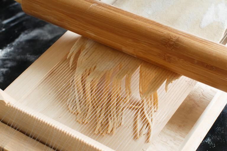 Making spaghetti alla chitarra with a tool - specialty of Abruzzo region