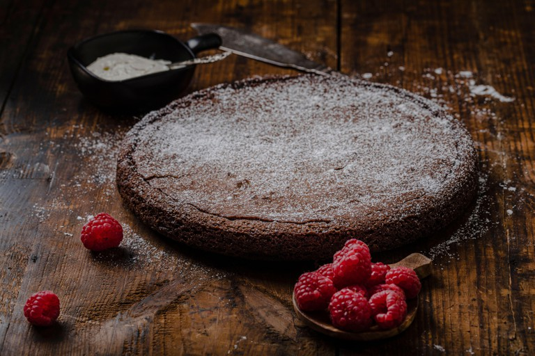 Chocolate mud cake, swedish kladdkaka or sticky chocolate cake with powdered sugar. The cake is on a rustic, vintage wooden table with raspberries and
